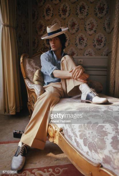 English singer Mick Jagger of the Rolling Stones sitting on a chaise longue in a panama hat and twotone shoes October 1973