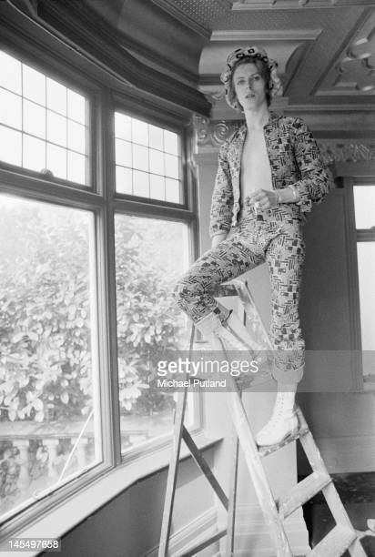 English singer, musician and actor David Bowie paints the coving of his ground floor flat at Haddon Hall in silver paint, Beckenham, south-east...