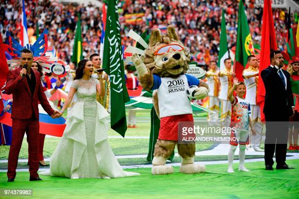 English singer Robbie Williams performs with Russian soprano Aida Garifullina as Brazilian football ledgend Ronaldo waves during the opening ceremony...