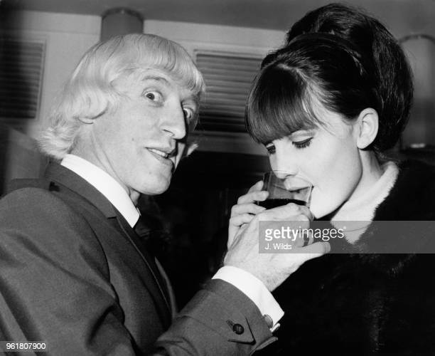 English singer Sandie Shaw accepts a drink from disc jockey Jimmy Savile at a Variety Club of Great Britain luncheon at the Savoy Hotel in London...