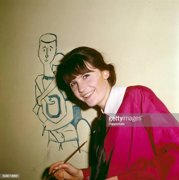 English singer Sandie Shaw pictured painting a mural on a wall of her house in 1965