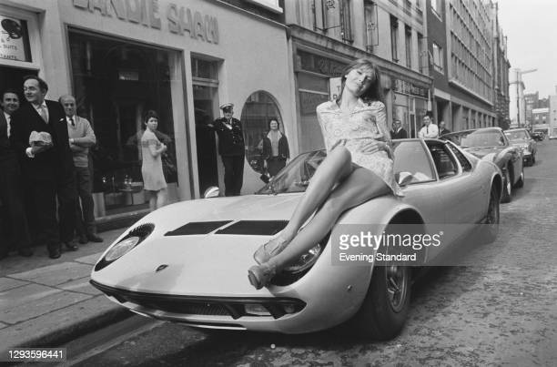English singer Sandie Shaw poses on the bonnet of a Lamborghini Miura during a press launch for her first fashion collection outside her boutique in...