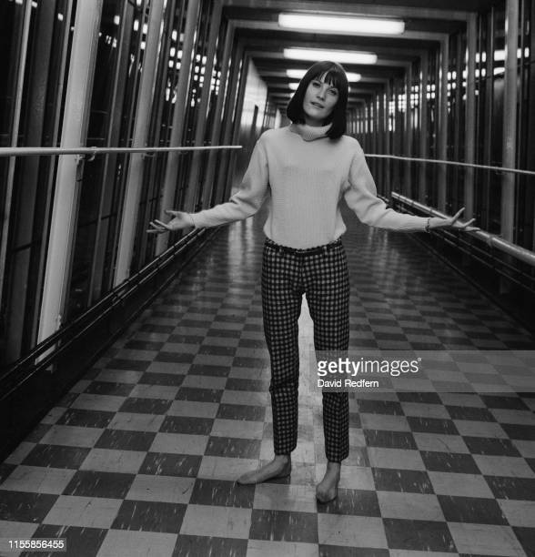 English singer Sandie Shaw wearing highneck sweater and checked trousers poses barefoot in the footbridge at Newport Pagnell service area on the M1...