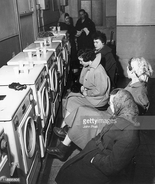 English singer Sheila Buxton joins a group of women sitting wearing overcoats in front of a row of washing machines in a launderette England March...