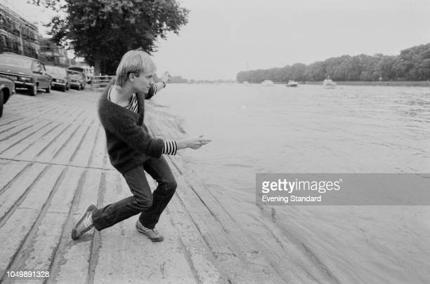 English singer, songwriter, and actor Sting throwing pebbles in a river, UK, 26th September 1979.