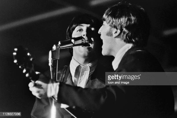 English singer songwriter and bassist Paul McCartney and English singer songwriter and guitarist John Lennon of the Beatles onstage in one of their...