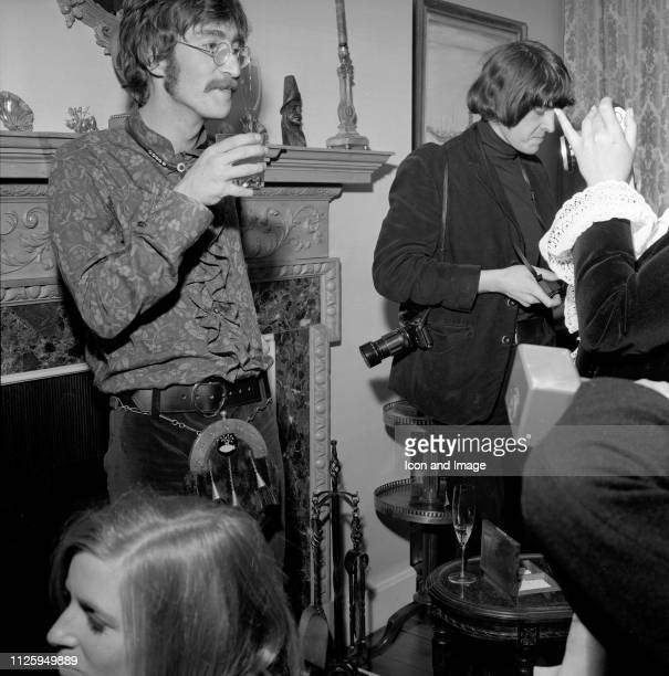 English singer songwriter and guitarist John Lennon of the Beatles stands beside Linda McCartney on the day that she meets her future husband Paul...
