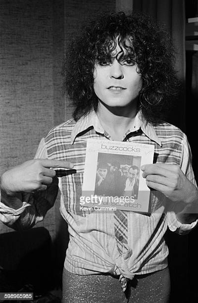 English singer songwriter and guitarist Marc Bolan holding a copy of the 'Spiral Scratch' EP the debut release by English punk rock group Buzzcocks...
