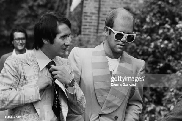 English singer songwriter pianist and composer Elton John and his manager John Reid on their way to a luncheon in honour of Buddy Holly at the...