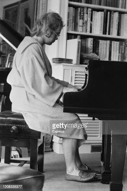 English singer songwriter pianist and composer Elton John wearing bathrobe play the piano at home UK 16th March 1973