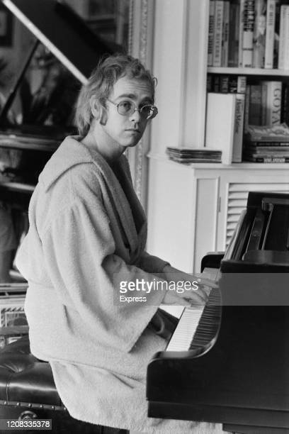 English singer songwriter pianist and composer Elton John wearing bathrobe play the piano at his home UK 16th March 1973