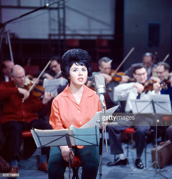 English singer Susan Maughan pictured in a recording studio with a string section of an orchestra behind her in 1963