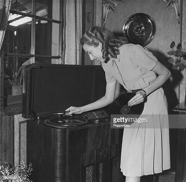 England WWII Forces Sweetheart singer Vera Lynn poses for a photoshoot at her home Vera places a record on her radiogram