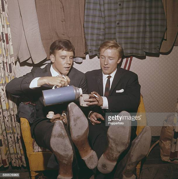 English singers Mike Sarne and Marty Wilde share a cigarette and hot drink from a thermos flask backstage in their dressing room before a concert...