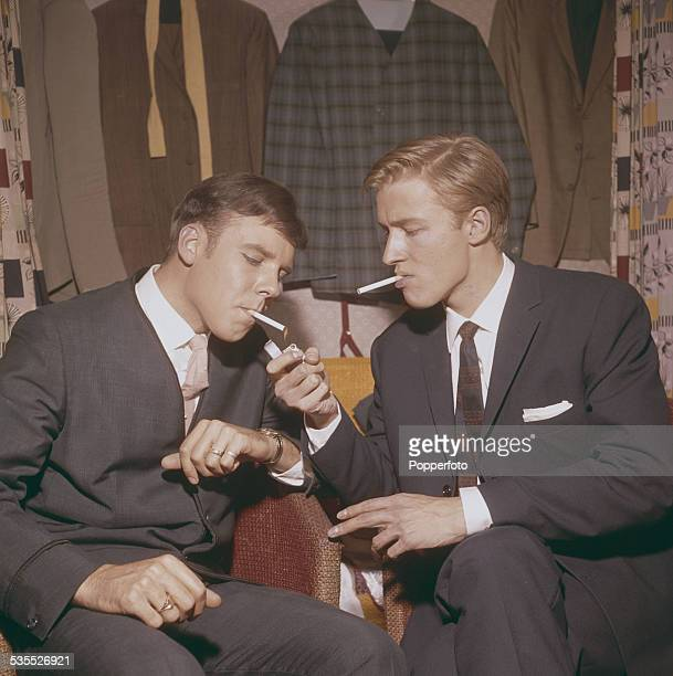 English singers Mike Sarne and Marty Wilde smoke cigarettes together backstage in their dressing room before a concert performance in England in 1962