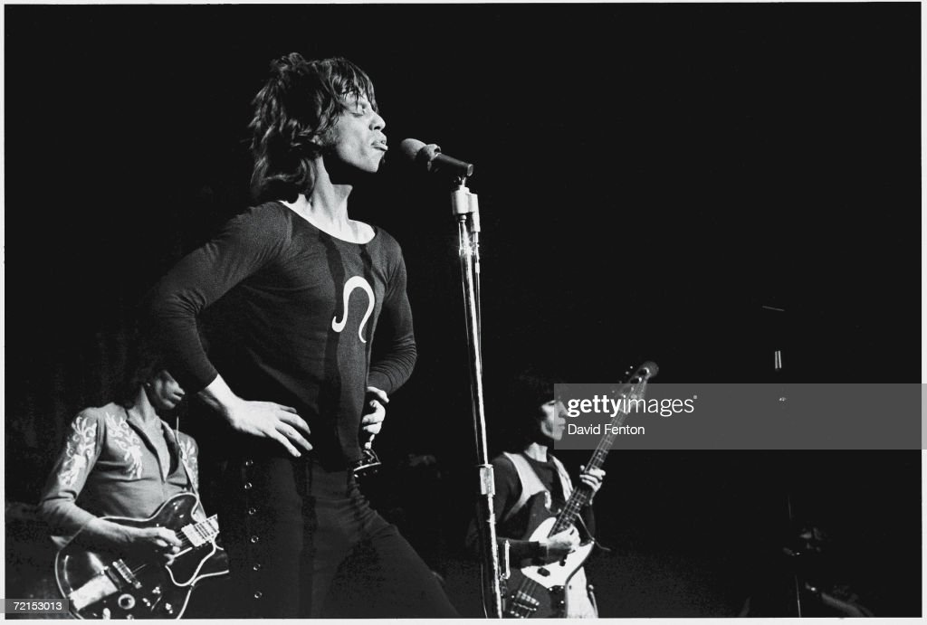 English singers, musicians, and songwriters Mick Jagger (at microphone), Keith Richards and Bill Wyman (far right) of the rock band 'The Rolling Stones,' perform on stage at Madison Square Garden, November 28, 1969. Jagger stands with his hands on his hips, eyes closed, and lips pursed together as he sings.