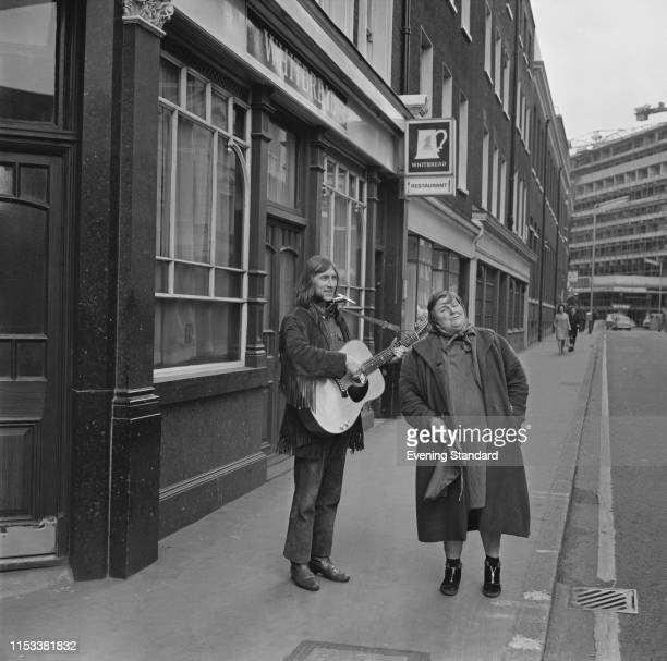 English singersongwriter and musician Dave Brock of space rock band Hawkwind playing an acoustic guitar with Meg Aitken outside a pub called...