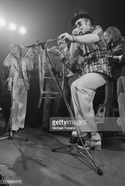 English singersongwriter and pianist Elton John performs on stage with from left manager John Reid Tony King and Muff Winwood at the Rocket Records...
