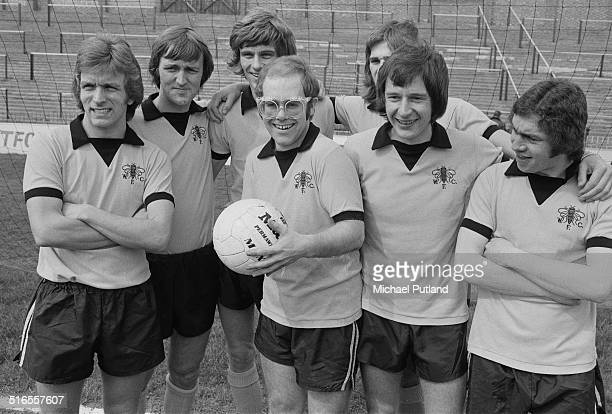 English singer-songwriter, and vice-president of Watford FC, Elton John at the Vicarage Road stadium in Watford with some of the players, April 1974.
