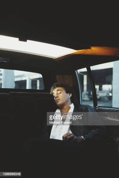 English singersongwriter Andrew Ridgeley of Wham pictured sleeping in the back seat of a limousine car during the North American leg of the pop duo's...