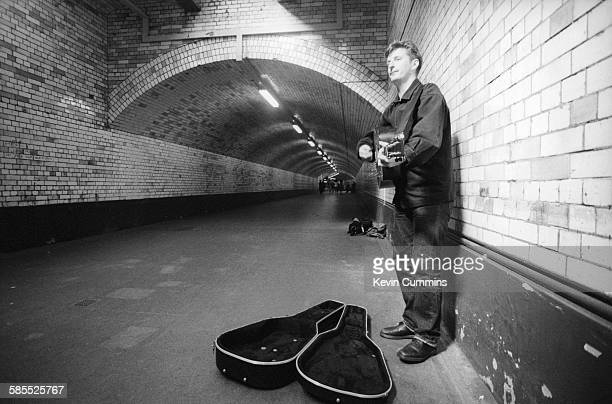 English singersongwriter Billy Bragg busking in the pedestrian tunnel at South Kensington tube station London circa 1990