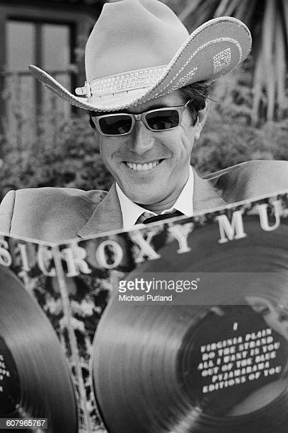 English singersongwriter Bryan Ferry wearing a stetson and looking at a copy of 'Roxy Music Greatest Hits' Los Angeles California October 1977