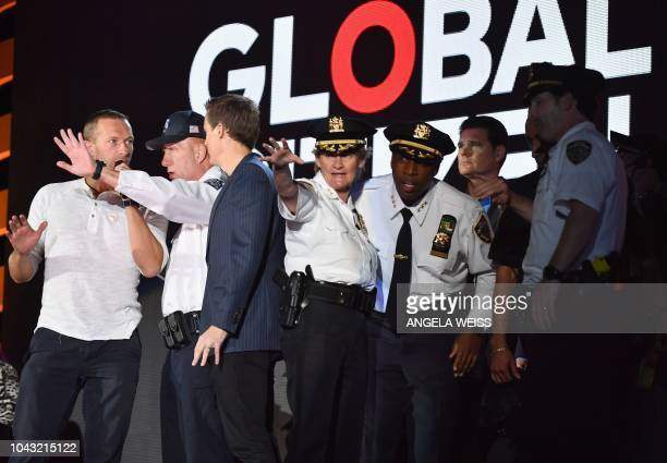 English singer-songwriter Chris Martin speaks onstage with NYPD officers after the crowd panicked when a security barrier fell during the 2018 Global...