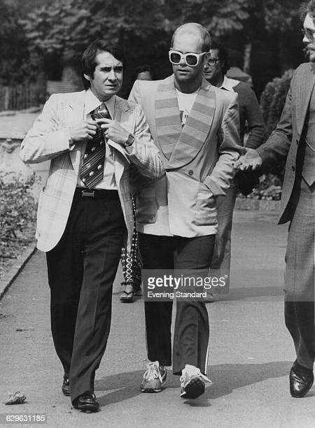 English singersongwriter Elton John with his manager John Reid on their way to a luncheon in honour of Buddy Holly at the Orangery in Holland Park...