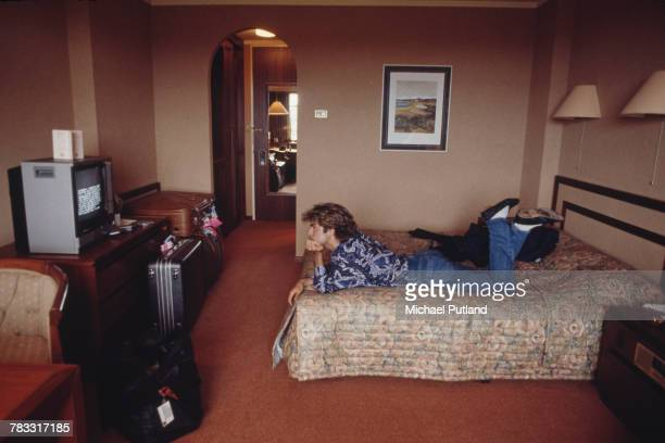English singersongwriter George Michael of Wham lies on a bed watching television in a hotel room in Sydney Australia during the pop duo's 1985 world...