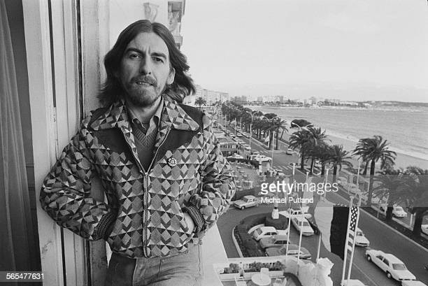 English singersongwriter guitarist and former Beatle George Harrison on a hotel balcony in Cannes France 30th January 1976 Harrison is in Cannes for...