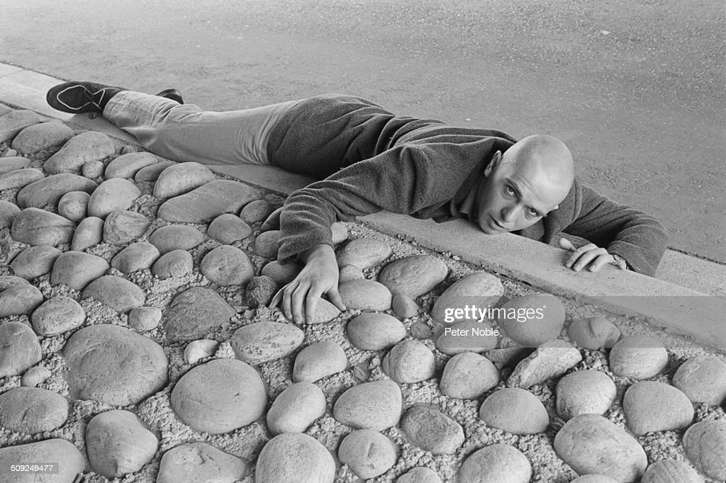English singer-songwriter, musician, and activist, Peter Gabriel, reclining on a curb, circa 1980.