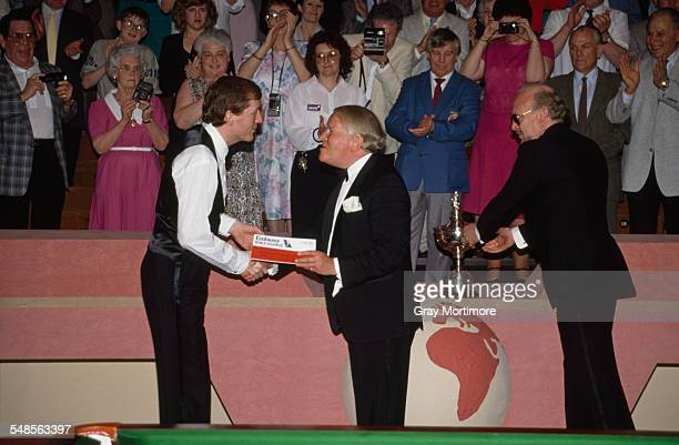 English snooker player Steve Davis is presented with the trophy after winning the final of the Embassy World Snooker Championship, Sheffield, 1st May...