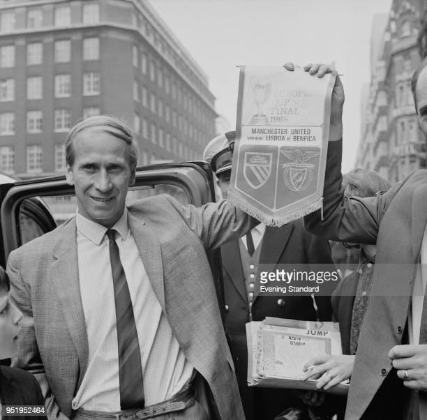 English soccer player Bobby Charlton of Manchester United FC holding a commemorative pennant of the European Cup final against SL Benfica, London,...