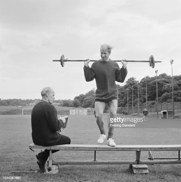 English soccer player Bobby Charlton of Manchester United FC training with a barbell with trainer Jack Crompton UK 1st August 1968