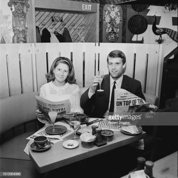 English soccer player Geoff Hurst with his wife Judith at a cafe while reading newspaper celebrating England's victory at the 1966 FIFA World Cup...