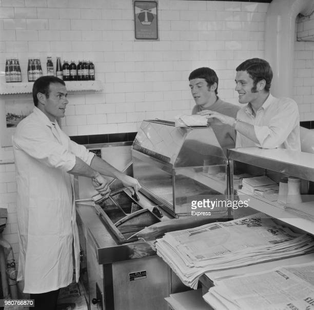 English soccer player George Curtis of Coventry City FC serving fish and chips to fellow teammates Jeff Blockley and Billy Rafferty at his shop UK...