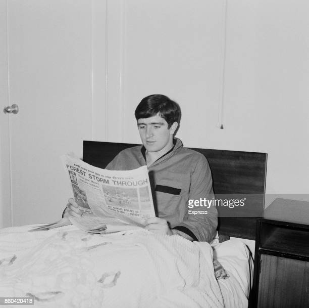 English soccer player Ian StoreyMoore of Nottingham Forest FC lying in bed while reading a newspaper titled 'Forest storm through' UK 10th April 1967
