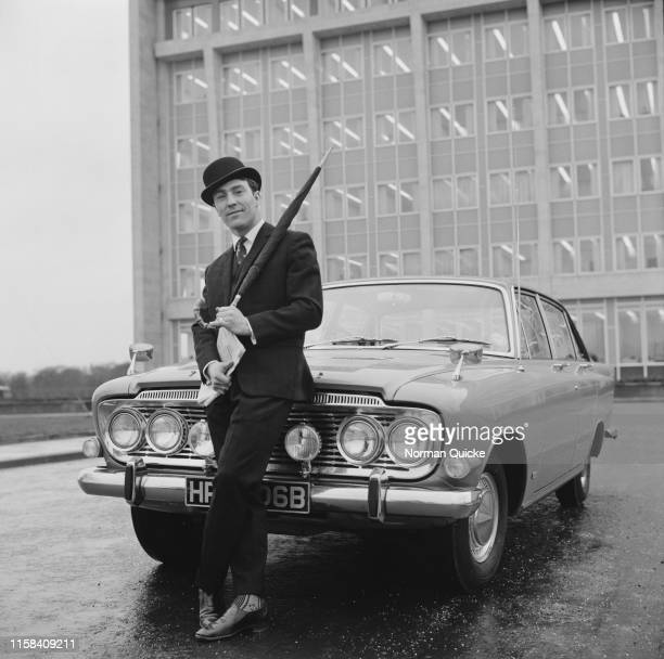 English soccer player Jimmy Greaves of Tottenham Hotspur FC stands next to a car wearing formal outfit wit umbrella and bowler hat, UK, 5th February...