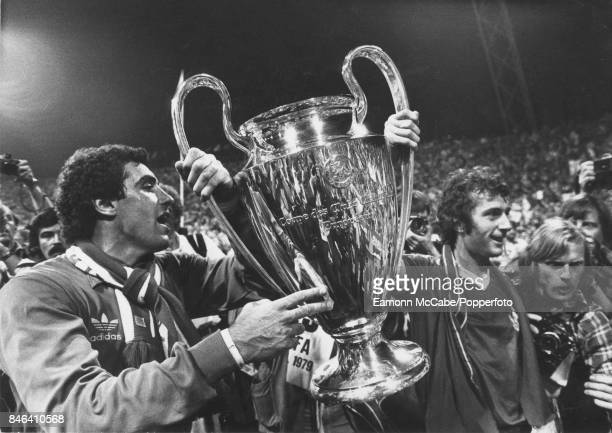 English soccer players Peter Shilton and Trevor Francis, both of Nottingham Forest, as they hold up the European Cup on the field in the...