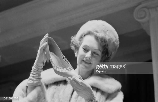 English socialite Raine McCorquondale Lady Lewisham and later Raine Spencer pictured trying on shoes in a shoe shop in England on 8th January 1963