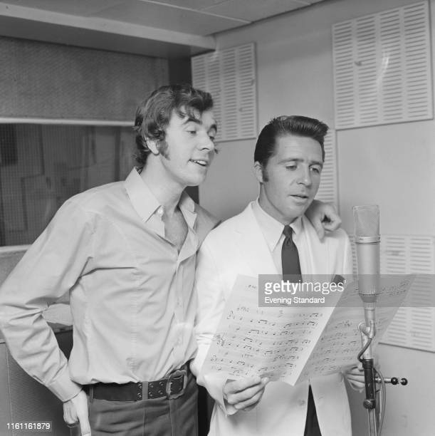 English songwriter Barry Mason and South-African professional golfer Gary Player singing together in a recording studio during the recordings of...