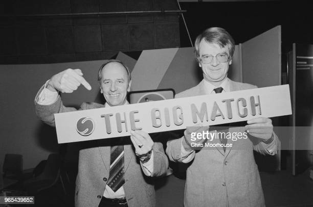 English sports commentator and television presenter Brian Moore and head of ITV Sport John Bromley holding a banner for soccer television programme...