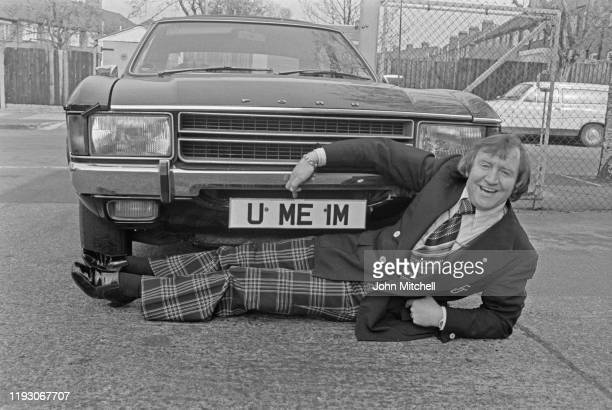 English standup comedian Jimmy Jones lying next to a car with U ME IM license plate UK 8th March 1977