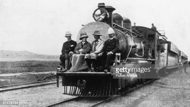 English statesman Joseph Chamberlain travelling on the cowcatcher at the front of a train during a visit to Uganda in his capacity as Colonial...