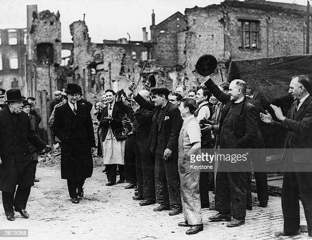 English statesman Sir Winston Churchill is greeted by a crowd during a visit to a bomb damaged area of Manchester