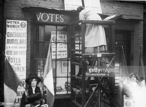 English suffragette Estelle Sylvia Pankhurst stands on a platform to paint the front of the Women's Social Defence League premises in Bow Road East...