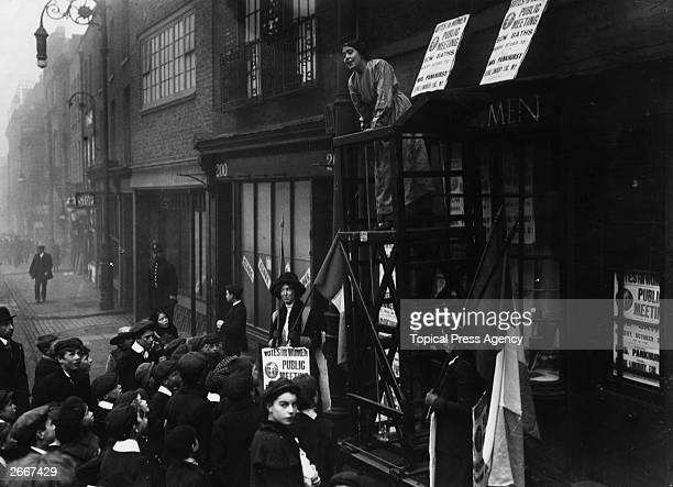 English suffragette Estelle Sylvia Pankhurst takes a break from painting the front of the Women's Social Defence League premises in Bow Road East...