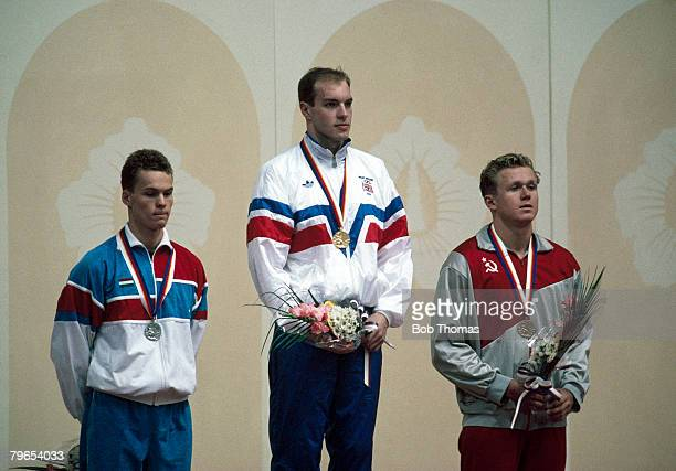 English swimmer Adrian Moorhouse of the Great Britain team stands on the podium after coming first to win the gold medal, with Karoly Guttler of...