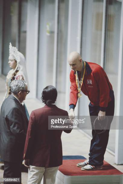 English swimmer Duncan Goodhew shakes the hand of an official on the medal podium after finishing in first place to win the gold medal for the Great...