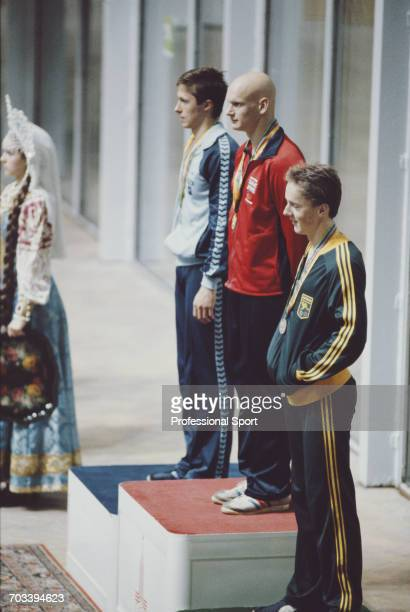 English swimmer Duncan Goodhew stands in centre on the medal podium with silver medallist Arsens Miskarovs of the Soviet Union on left and bronze...